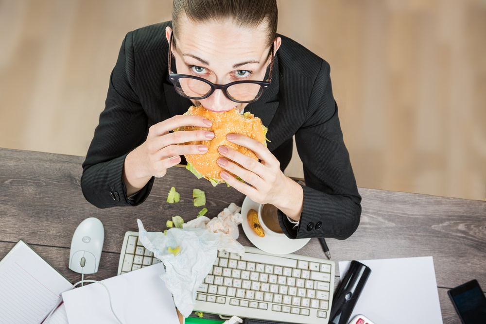 woman-eating-junk-food-at-desk