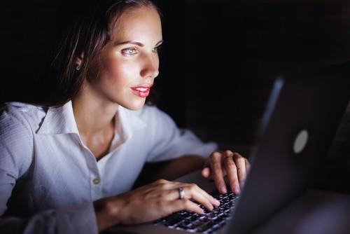 woman using computer at night