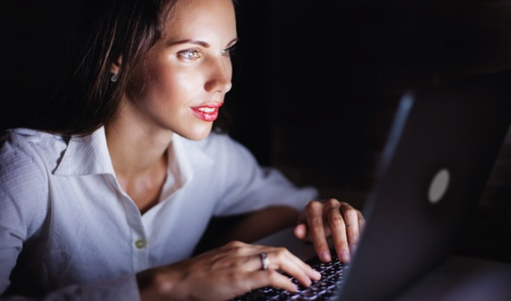 woman using computer at night