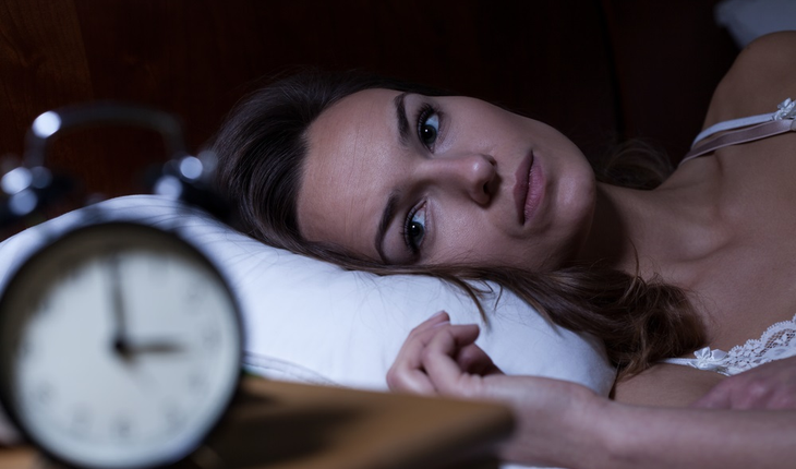 woman with insomnia and alarm clock