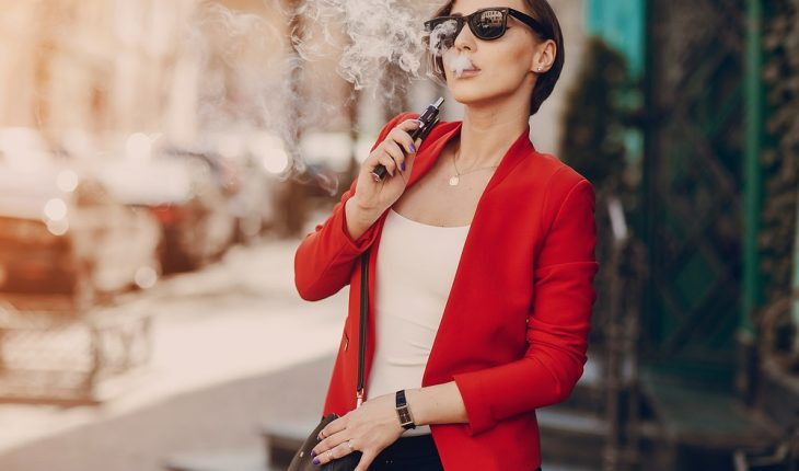 young-woman-vaping-in-street
